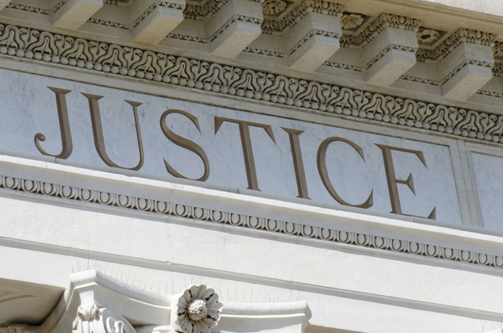 side of a courthouse with the word justice